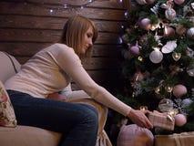 一个美丽的白肤金发的女孩投入礼物在圣诞树下 美丽的首饰和玩具,轻的诗歌选 免版税图库摄影