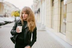 一个美丽的白肤金发的女孩的画象在城市街道上的,在她的手上拿着一纸杯 免版税库存图片