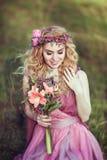 一个美丽的白肤金发的女孩的画象一件桃红色礼服的有花束的 库存照片
