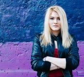 一个美丽的白肤金发的女孩的画象在紫色桃红色墙壁附近的有被交叉的双臂的 免版税库存照片