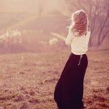一个美丽的白肤金发的女孩的画象白色套头衫的,站立与他的  图库摄影