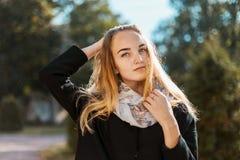 一个美丽的白肤金发的女孩的画象黑外套的 免版税库存图片