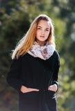 一个美丽的白肤金发的女孩的画象黑外套的 免版税库存照片