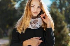 一个美丽的白肤金发的女孩的画象黑外套的 库存图片