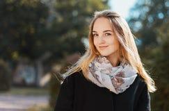 一个美丽的白肤金发的女孩的画象黑外套的 免版税图库摄影