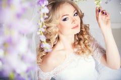 一个美丽的白肤金发的新娘的照片一套豪华婚礼礼服的在内部 图库摄影