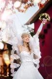 一个美丽的白肤金发的新娘的画象有婚礼bouqet的 库存图片