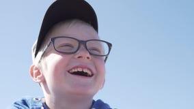 一个美丽的白肤金发的男孩的面孔的特写镜头在街道上的 股票视频
