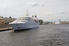一个美丽的白色巡航划线员在一个船坞站立在城市 库存照片