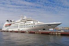 一个美丽的白色巡航划线员在一个船坞站立在城市 免版税库存照片