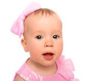 一个美丽的矮小的女婴的面孔有被隔绝的一把桃红色弓的 免版税库存图片