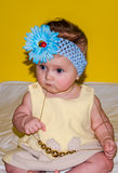 一个美丽的矮小的女婴的画象一件黄色礼服的有在她的头和首饰的一把弓的成串珠状在他的脖子上 图库摄影