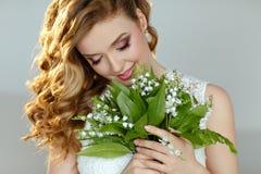 一个美丽的精美白肤金发的微笑的女孩的画象有百合的 库存照片