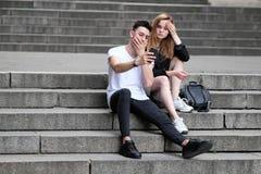 一个美丽的红发女孩和一个深色的人看了事有趣在他们的手机 库存图片