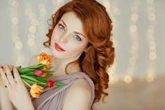 一个美丽的红发女孩的画象有举行a的蓝眼睛的 图库摄影
