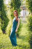 一个美丽的红发少妇的画象一件绿色礼服的 免版税库存照片