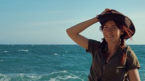 一个美丽的红发旅客女孩的画象一个牛仔帽的在海海滩 股票视频