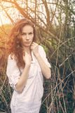 一个美丽的红头发人卷曲女孩的室外画象 免版税库存图片