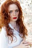 一个美丽的红头发人女孩和在一件白色衬衣的红色唇膏的逗人喜爱的画象有构成的在开花的树中的庭院里  图库摄影