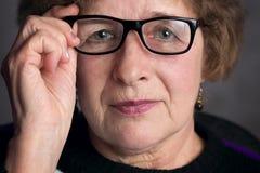 一个美丽的老妇人的画象戴眼镜的 免版税库存照片