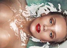 一个美丽的肉欲的迷人的金发碧眼的女人的画象在水, vogu中 免版税库存照片