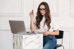 一个美丽的苗条女孩在一个绝尘室戴在便装样式穿戴的宽时髦的眼镜,坐在一张桌上 免版税库存图片