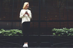 一个美丽的苗条女孩站立在咖啡馆附近和谈话在电话和等待她的男朋友 图库摄影