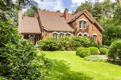 一个美丽的英国样式房子的后院有灌木和gree的 库存图片