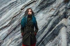 一个美丽的行家女孩的画象背景的岩石峭壁 被染的头发,蓝色,长期 免版税库存图片