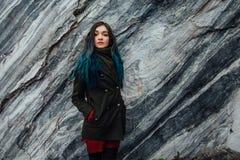 一个美丽的行家女孩的画象背景的岩石峭壁 被染的头发,蓝色,长期 库存图片