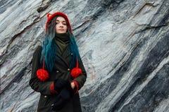一个美丽的行家女孩的画象背景的岩石峭壁 被染的头发,蓝色,长期 免版税库存照片