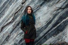 一个美丽的行家女孩的画象背景的岩石峭壁 被染的头发,蓝色,长期 图库摄影