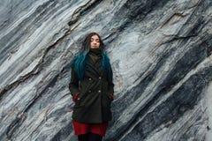 一个美丽的行家女孩的画象背景的岩石峭壁 被染的头发,蓝色,长期 免版税图库摄影