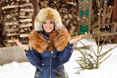 一个美丽的迷人的女孩的画象裘皮帽和红色co的 库存图片