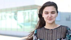 一个美丽的迷人的微笑的愉快的女孩,风的画象有美好的微笑的吹头发 股票录像