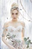 一个美丽的逗人喜爱的愉快的新娘的柔和的画象有美好的发型欢乐明亮的构成的在与的耳环的一套婚礼礼服 库存照片