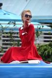 一个美丽的金发碧眼的女人的减速火箭的画象一辆蓝色汽车的 库存照片