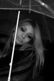 一个美丽的金发碧眼的女人的单色画象在一把透明伞下 库存图片