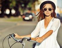一个美丽的金发碧眼的女人的室外时尚画象有自行车的 免版税库存图片