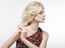 一个美丽的金发碧眼的女人的秀丽画象一件黑礼服的有红色的 免版税库存照片