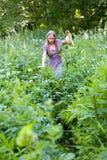 一个美丽的金发碧眼的女人通过高草丛林做她的方式 库存图片