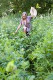 一个美丽的金发碧眼的女人通过高草丛林做她的方式 免版税图库摄影
