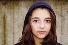 一个美丽的青少年的女孩的画象有一个黑敞篷的 免版税库存照片