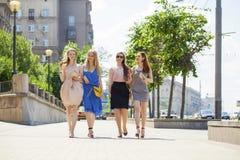 一个美丽的年轻人的画象四名妇女在夏天城市走 免版税库存图片