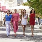 一个美丽的年轻人的画象四名妇女在夏天城市走 库存照片