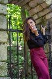 一个美丽的年轻和可爱的青少年的女孩的画象有长的头发的在被毁坏的石城堡的钢门附近在Striys 库存照片