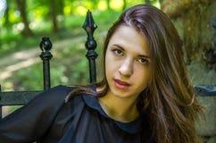一个美丽的年轻和可爱的青少年的女孩的画象有长的头发的在被毁坏的石城堡的钢门附近在Striys 库存图片
