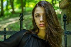 一个美丽的年轻和可爱的青少年的女孩的画象有长的头发的在被毁坏的石城堡的钢门附近在Striys 图库摄影