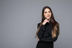一个美丽的年轻女商人的画象反对灰色背景的 免版税库存图片