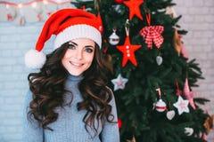 一个美丽的年轻微笑的女孩的画象圣诞老人帽子的 库存图片